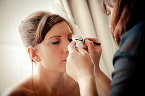 Bride having eye liner applied by Powder Beauty