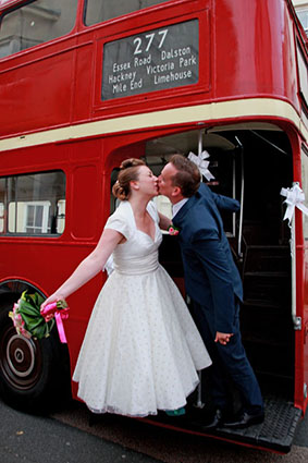 Bride and Groom on red double decker bus.